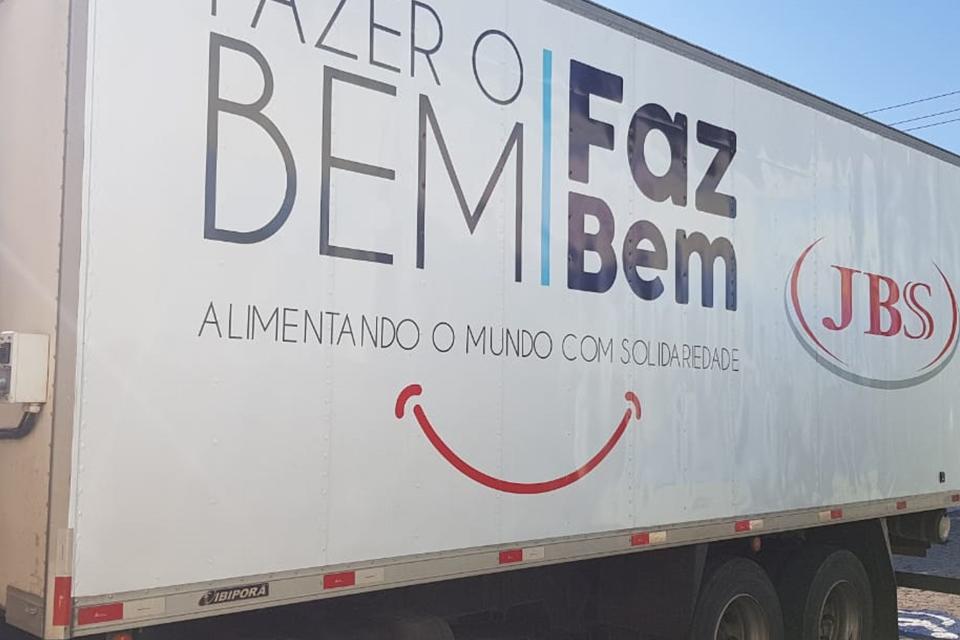 """Caminhão visto de lado com o logo """"Fazer o bem faz bem + JBS"""""""