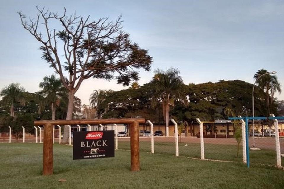 Campo e fazenda com árvores, na frente tem um tronco com uma placa da empresa Swift Black
