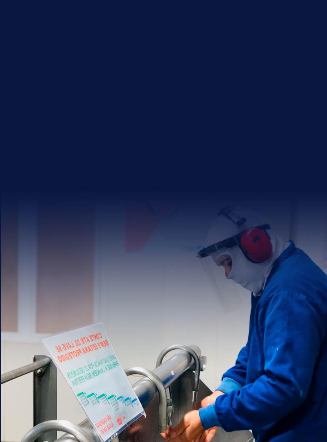 Homem trabalhando com roupa azul, mascará e protetor facil