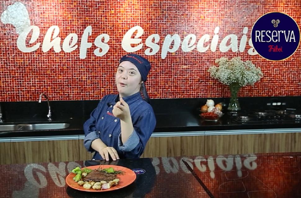 Pessoa em uma cozinha com roupa azul e touca, prato de comida em uma bancada. Na parede atrás está escrito Chefs Especiais.