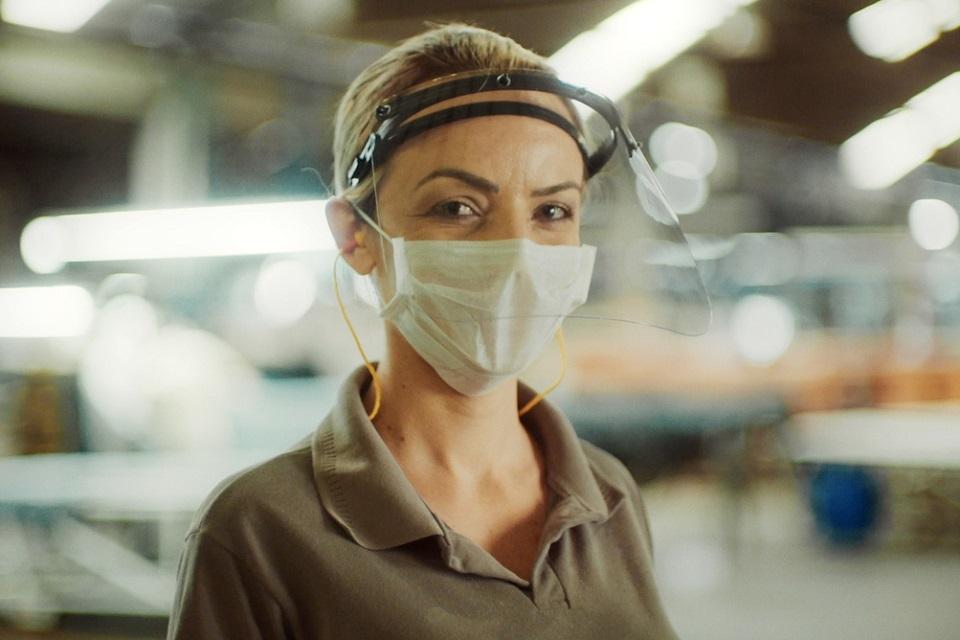 Moça com máscara e proteção facial de acrílico. Está vestindo uma camisa social marrom.