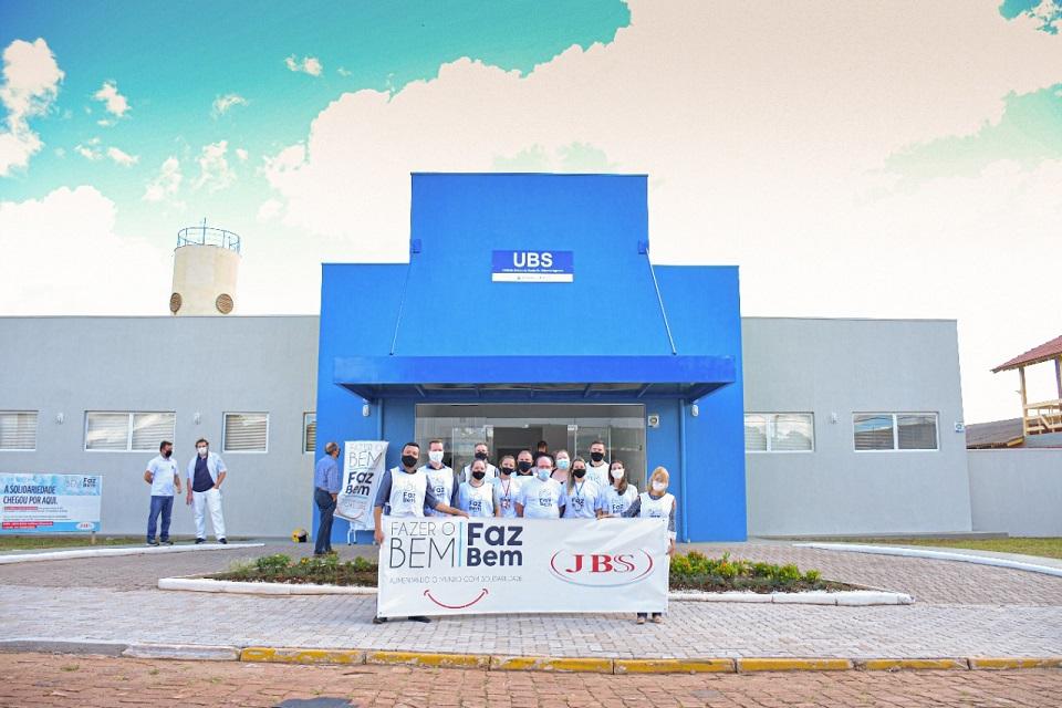 Fachada da UBS de RS na cor azul com pessoas na frente segurando uma faixa do Projeto Fazer o bem Faz Bem JBS.
