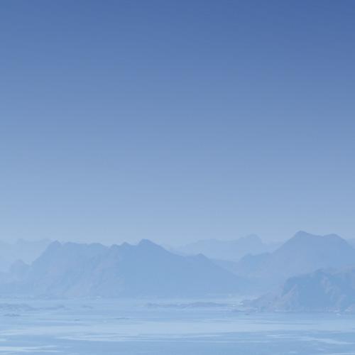 Céu azul e Montanhas ao fundo e um mar em baixo