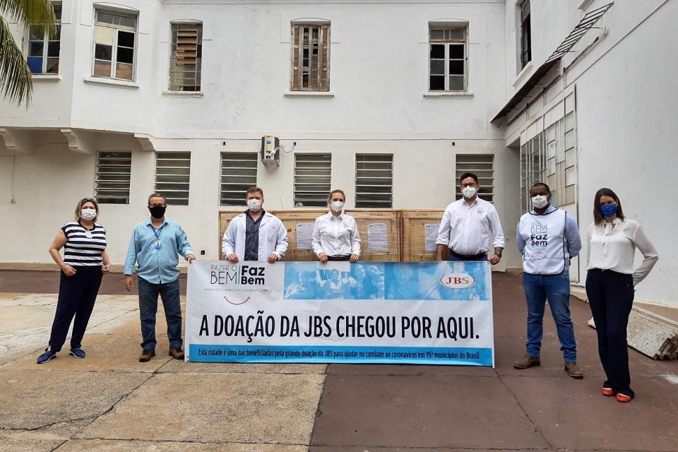 Pessoas de máscara segurando um cartaz escrito: Doação da JBS chegou por aqui