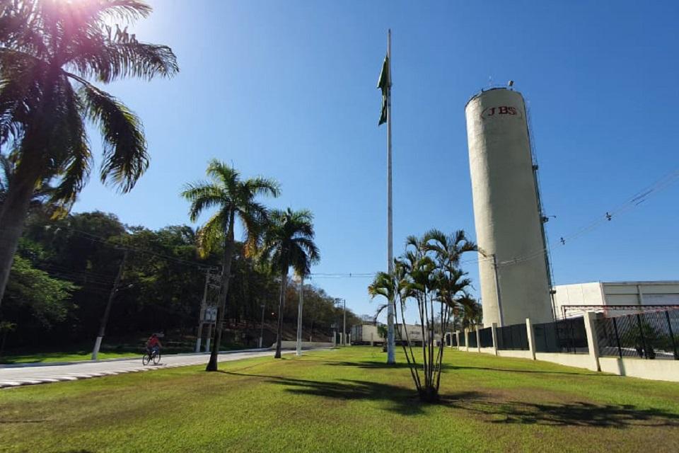 Jardim com árvores e um mastro com bandeira do Braisl, ao fundo uma torre com logo da JBS