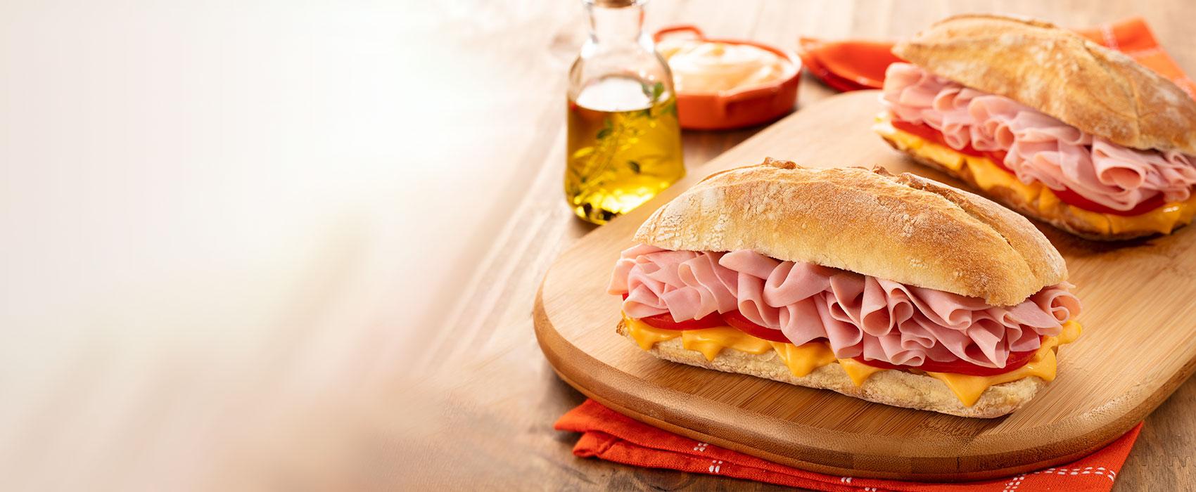 fundo com um pão com mortadela fatiada e queijo cheddar em cima de uma mesa