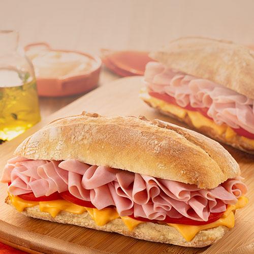 fundo com um pão com mortadela fatiada e queijo cheddar em cima de uma mesa mobile