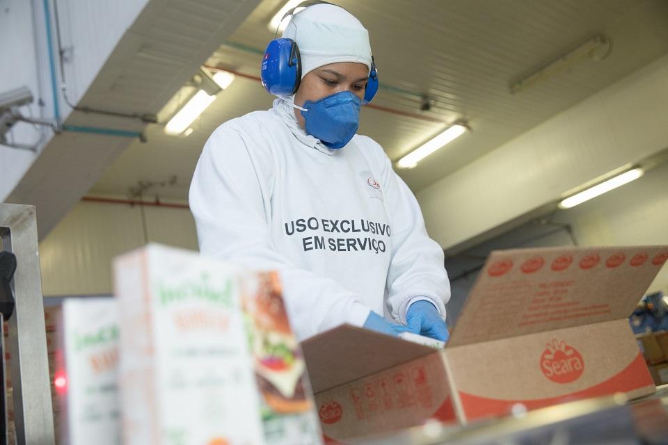 Pessoa usando roupas brancas, máscara e protetor de ouvido embalando produtos em uma caixa de papelão