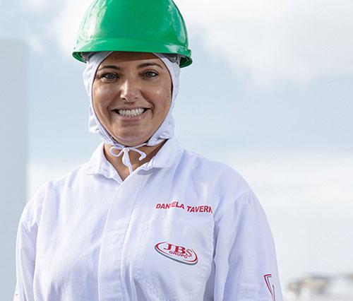 Mulher usando capacete verde e uniforme da JBS