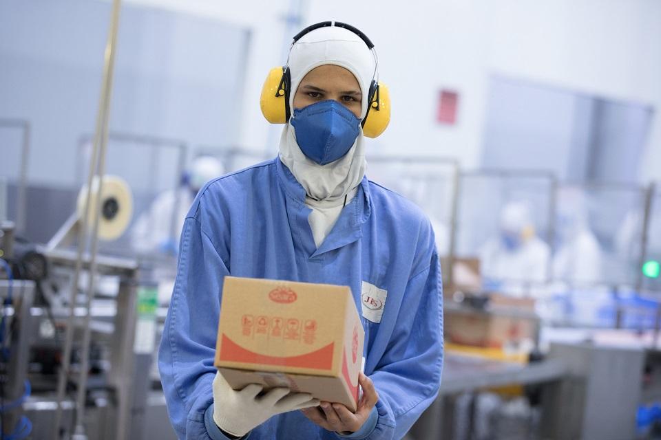 Homem usando aquipamentos de proteção e máscara segurando uma caixa da Seara