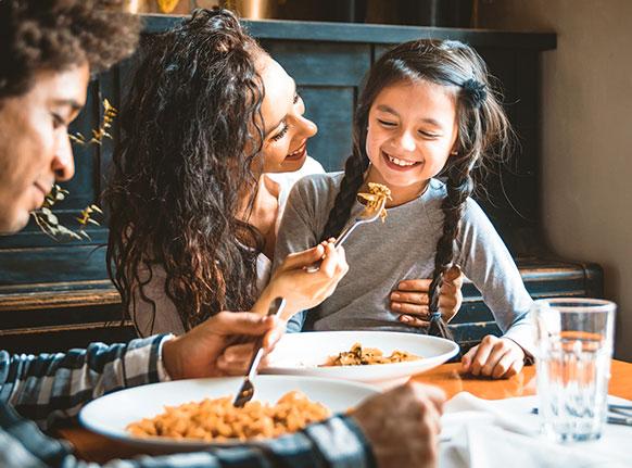 2 adultos e uma criança em uma mesa comendo comida